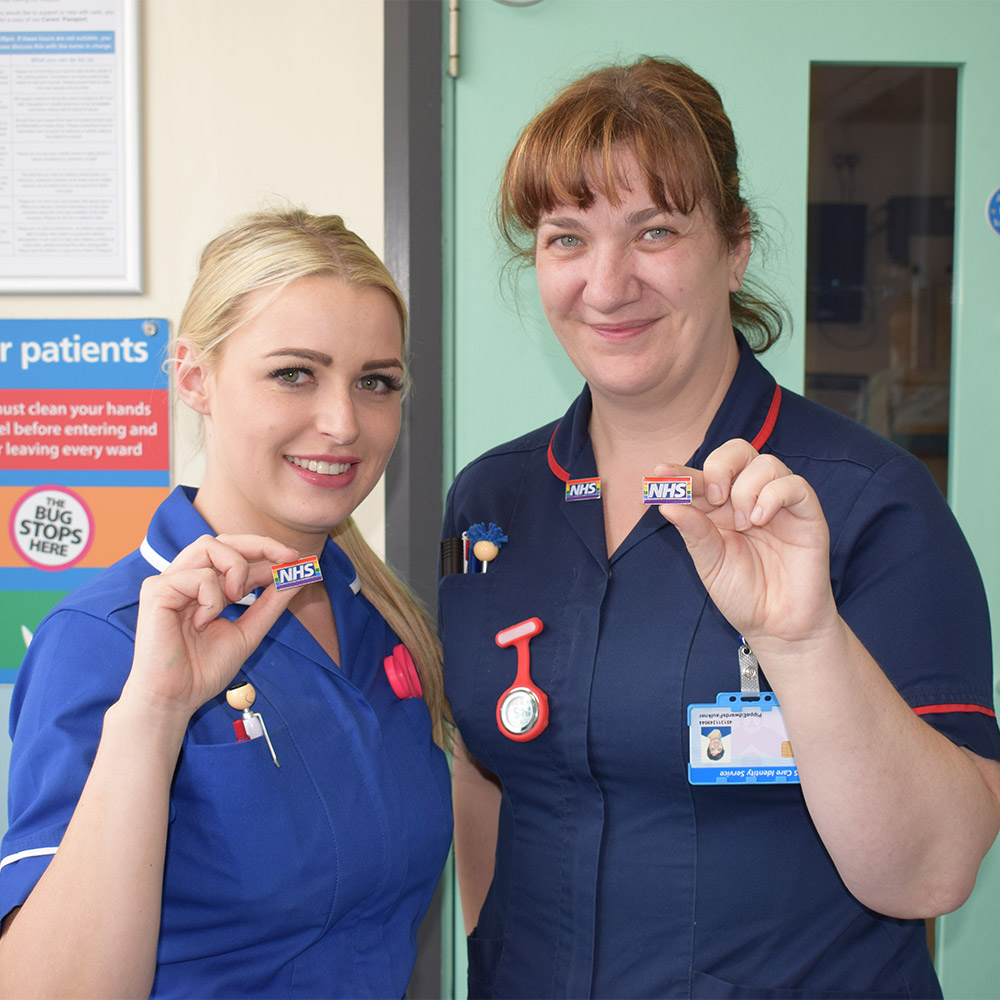 Two nurses holding NHS pins decorated for pride