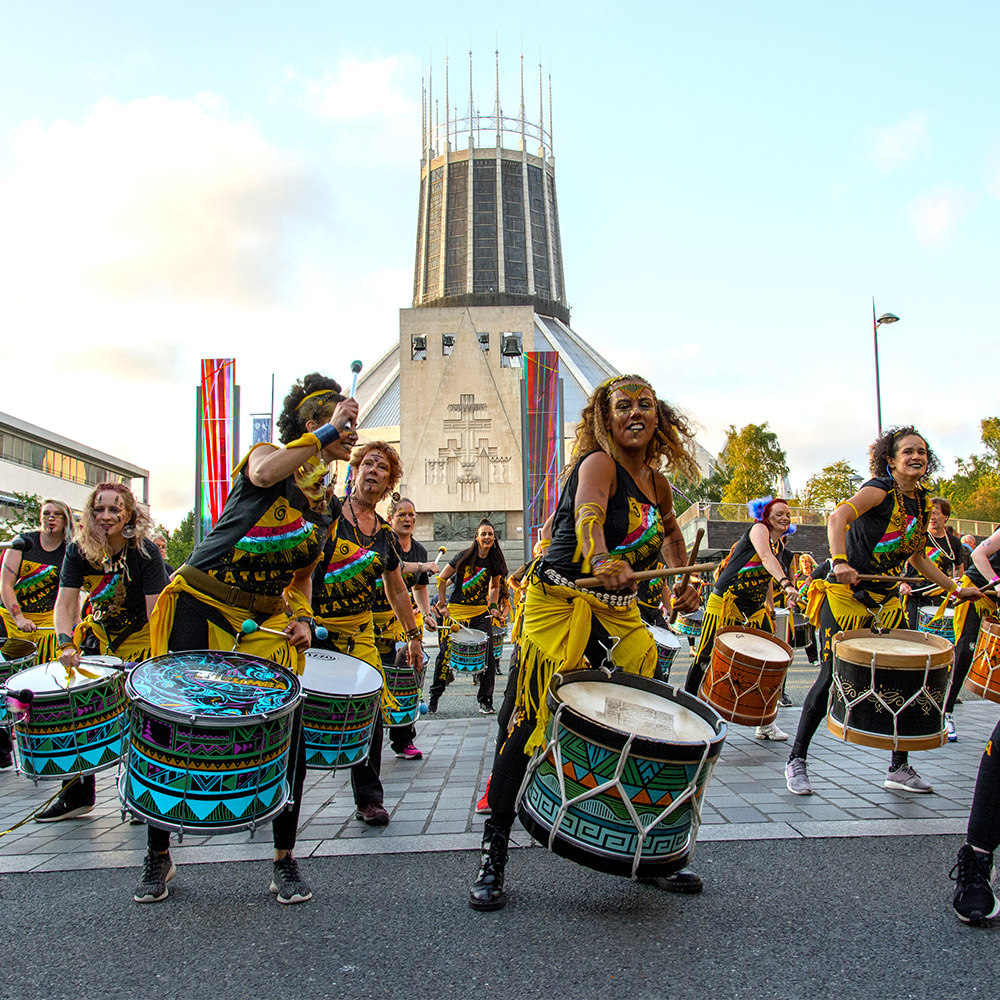 A group of drummers doing a high energy performance outside to the metropolitan cathedral